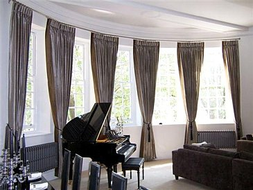 Large bay window with triple pleat curtains fitted to chrome poles